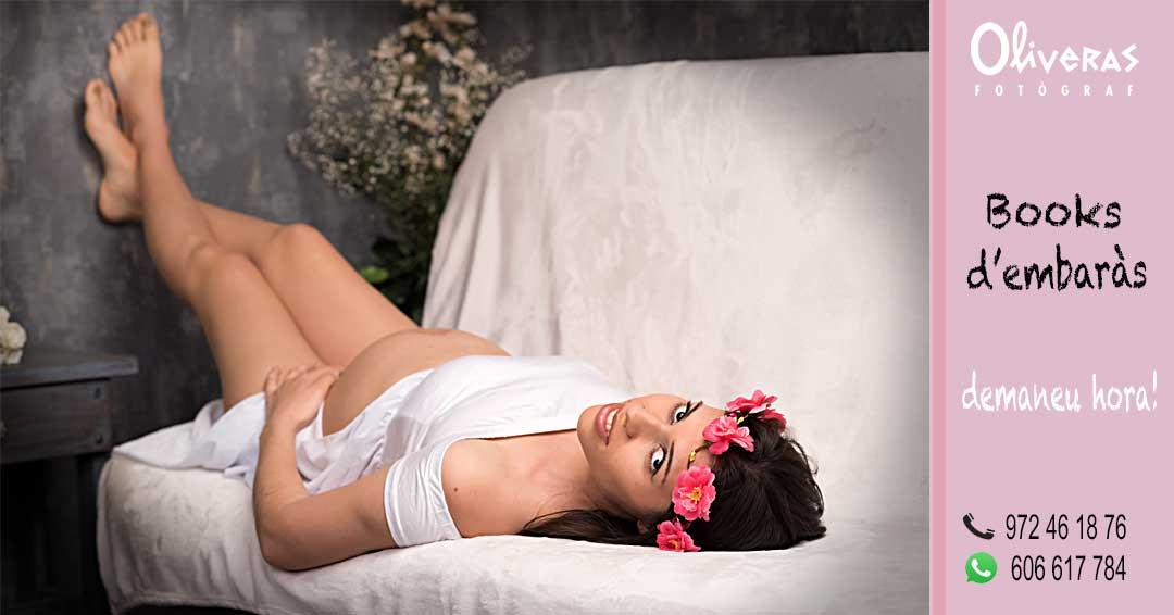 Embarassada en un sofà amb els peus enlaira descansa'n en la sessió de fotos a Oliveras fotògraf